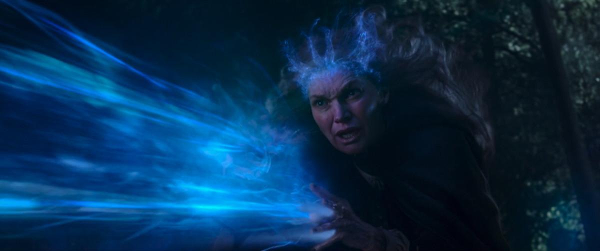 La madre de Agatha Harkness exhala magia azul de sus manos mientras le da una corona mágica azul en WandaVision.