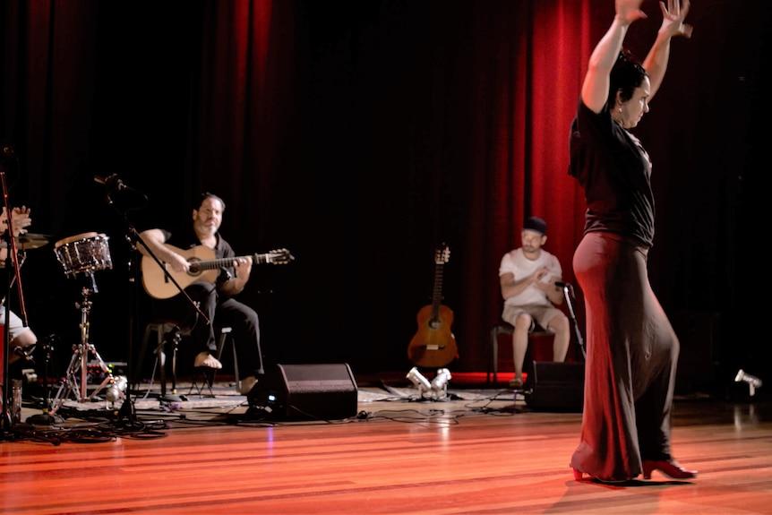 Una bailarina con las manos levantadas en el aire mientras los músicos tocan de fondo