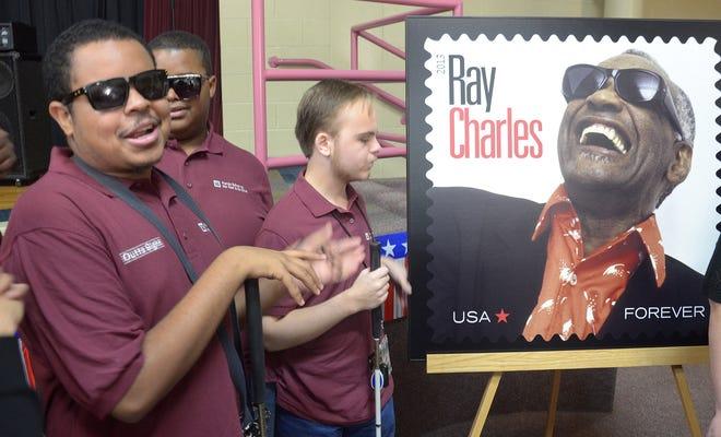 Daniel Tanner, cantante principal de Florida School of the Deaf and Blind Singing Out of Sight, se ríe junto a una copia de una estampilla conmemorativa del Servicio Postal de los EE. UU. En honor al músico Ray Charles durante una fiesta de inauguración celebrada en la FSDB en 2013 a la que asistió Charles. la escuela de 1937-1945.