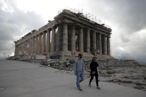 Los visitantes con máscaras faciales suben por la colina de la Acrópolis, con el Partenón de fondo en Atenas.  Archivo de imagen: AP Photo / Thanassis Stavrakis
