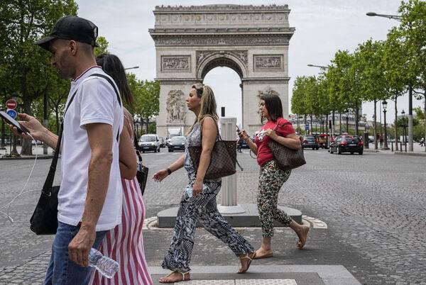 La gente cruza los Campos Elíseos en París el jueves.  El miércoles, Francia alivió varias restricciones de Covid.  Archivo de imagen: AP Photo / Michel Euler