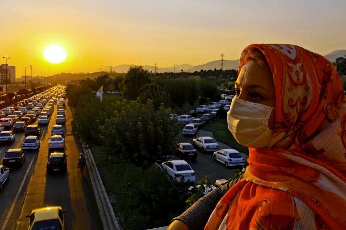 Un peatón enmascarado camina hacia su casa durante la hora pico en Teherán, mientras el lanzamiento de una vacuna insuficiente provoca la indignación pública.